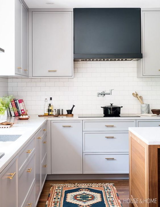 угловая белая кухня с ярким ковром