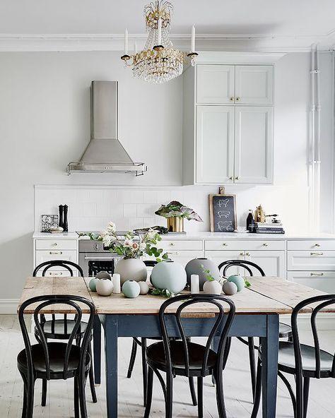 Просторная белая кухня с деревянным столом и хрустальной люстрой