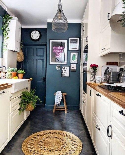 Окрашенные в синий цветы стены и дверь на фоне белой кухни